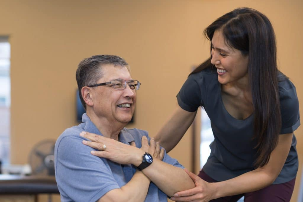 A female occupational therapist of Asian descent works with a cheerful senior male as he does exercises on an exercise ball. She is helping steady him as he crosses his arms.